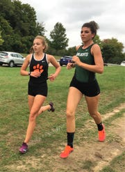 Novi's Katherine Ray (right) was third in 20:06 and Brighton's Morgan Crompton was fourth in 20:26 in a meet at Cass Benton Park on Tuesday, Oct. 2, 2018.