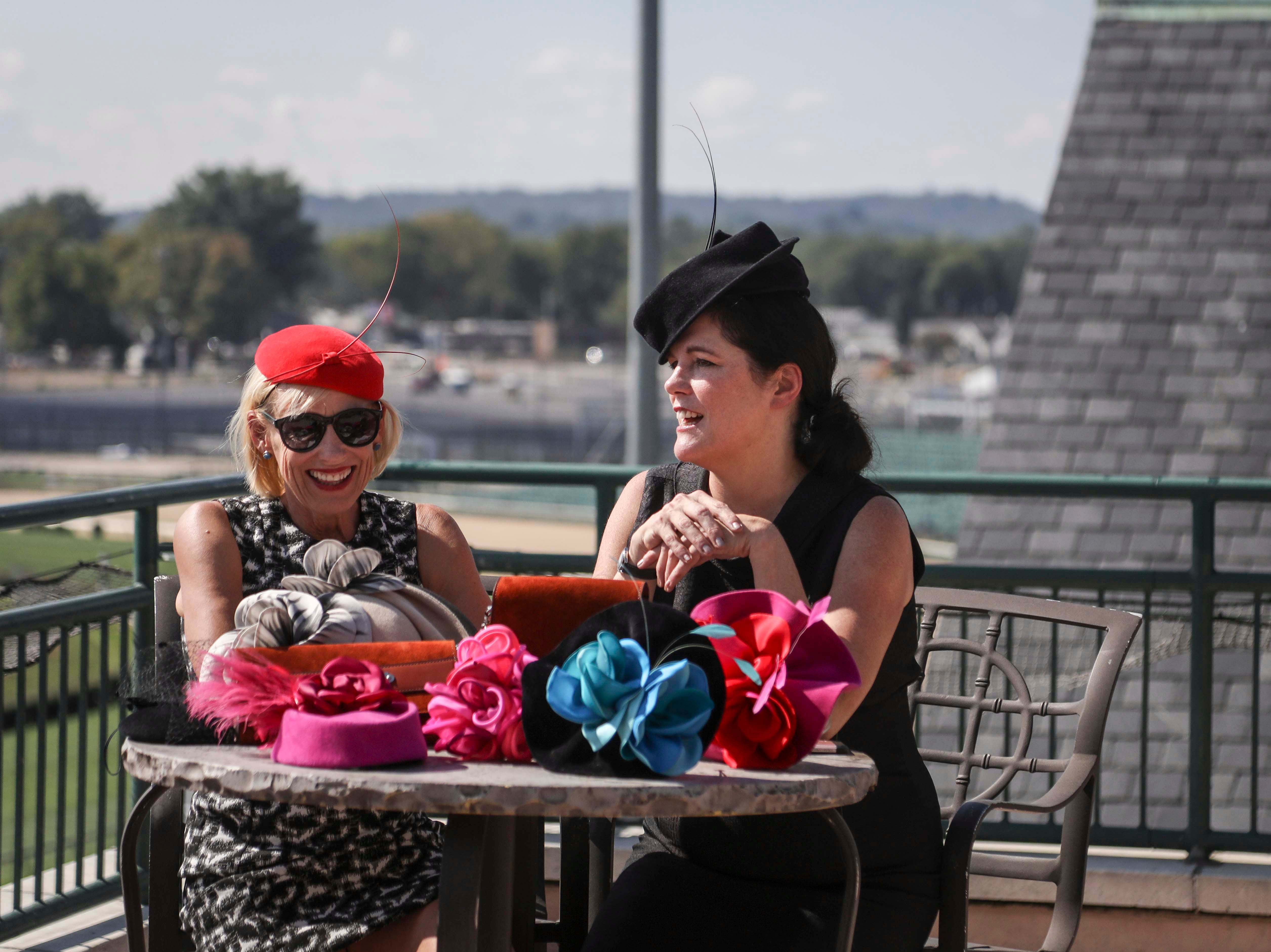 Kirby Adams, left, and Christine Moore, right, track fashion expert and owner of Cam Hats, discuss track fashion during an interview with the Courier Journal ahead of the Breeders Cup (November 3) at Churchill Downs on Wednesday, October 3, 2018.