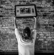 Danny Bodner removes an old horse racing photo from the walls of the Whirlaway Tavern. Sept. 11, 2018.