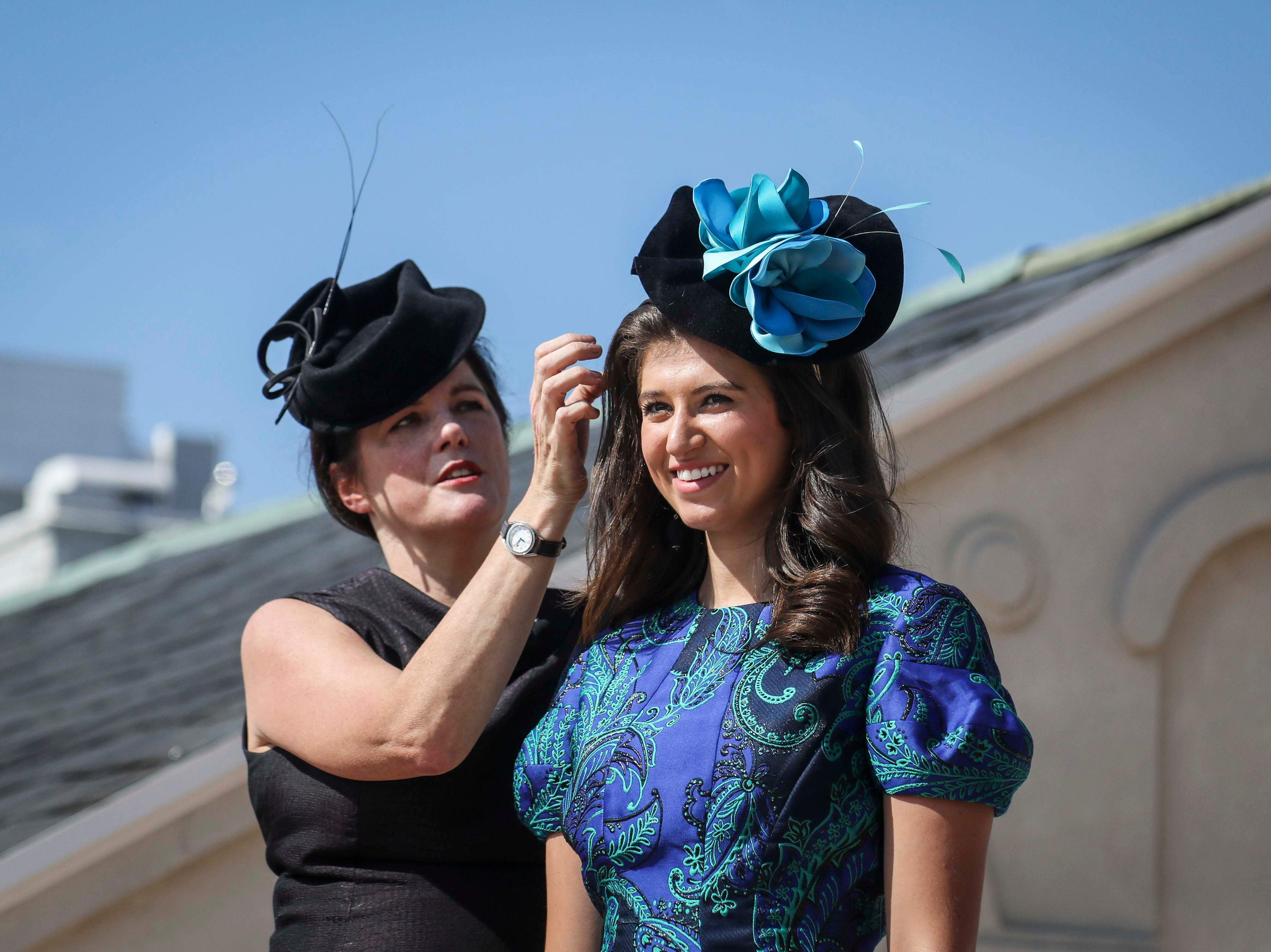 Christine Moore, left, track fashion expert and owner of Cam Hats, shows how to properly wear a fascinator on Katie Bouchard, Miss Kentucky, during an interview with the Courier Journal ahead of the Breeders Cup (November 3) at Churchill Downs on Wednesday, October 3, 2018.