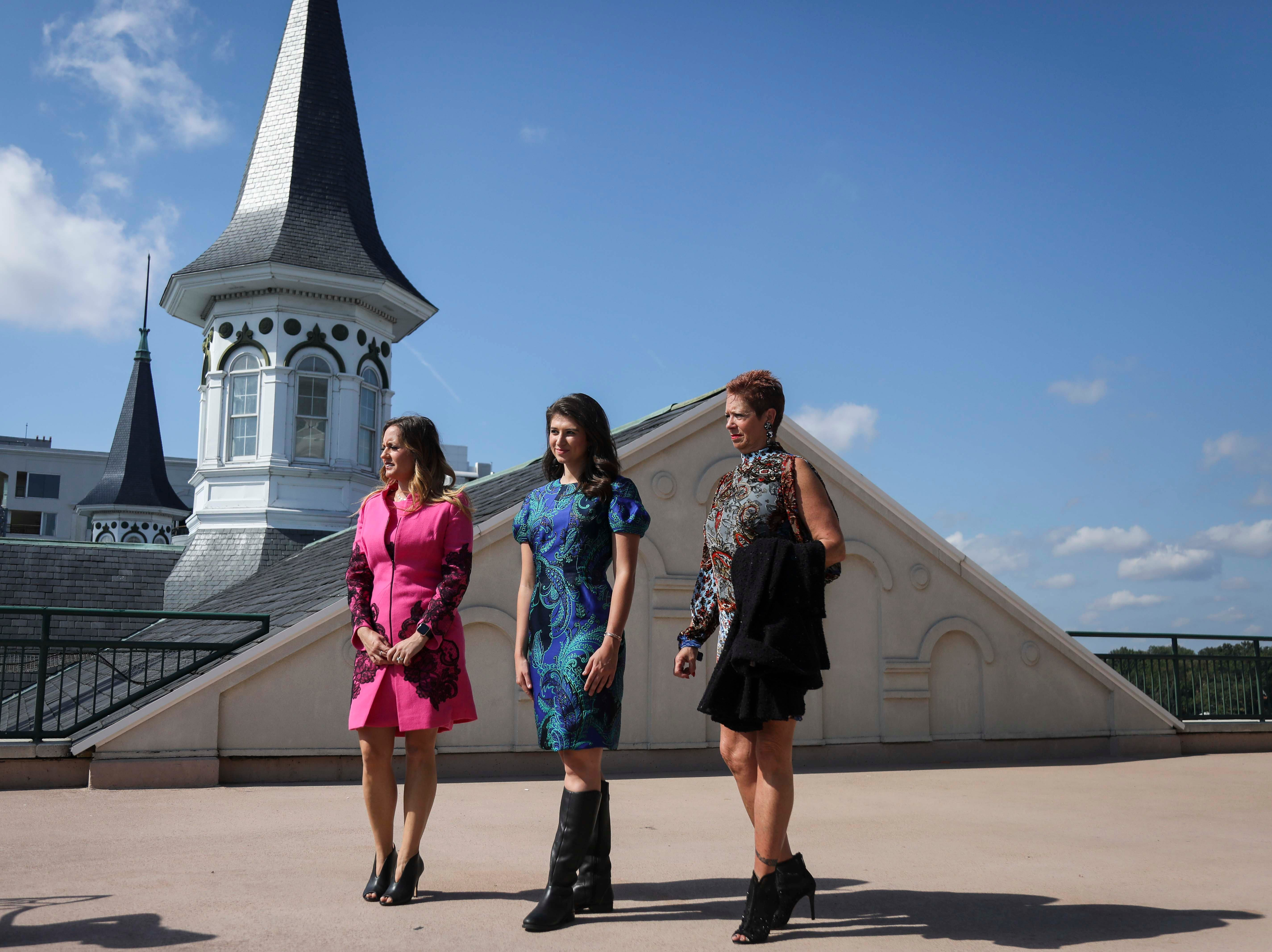 From left to right: Candice Isa, Katie Bouchard and Patty Ethington don dresses made by Lourdes Chavez and hats made by Christine Moore, track fashion expert and owner of Cam Hats, during an interview with the Courier Journal ahead of the Breeders Cup (November 3) at Churchill Downs on Wednesday, October 3, 2018.