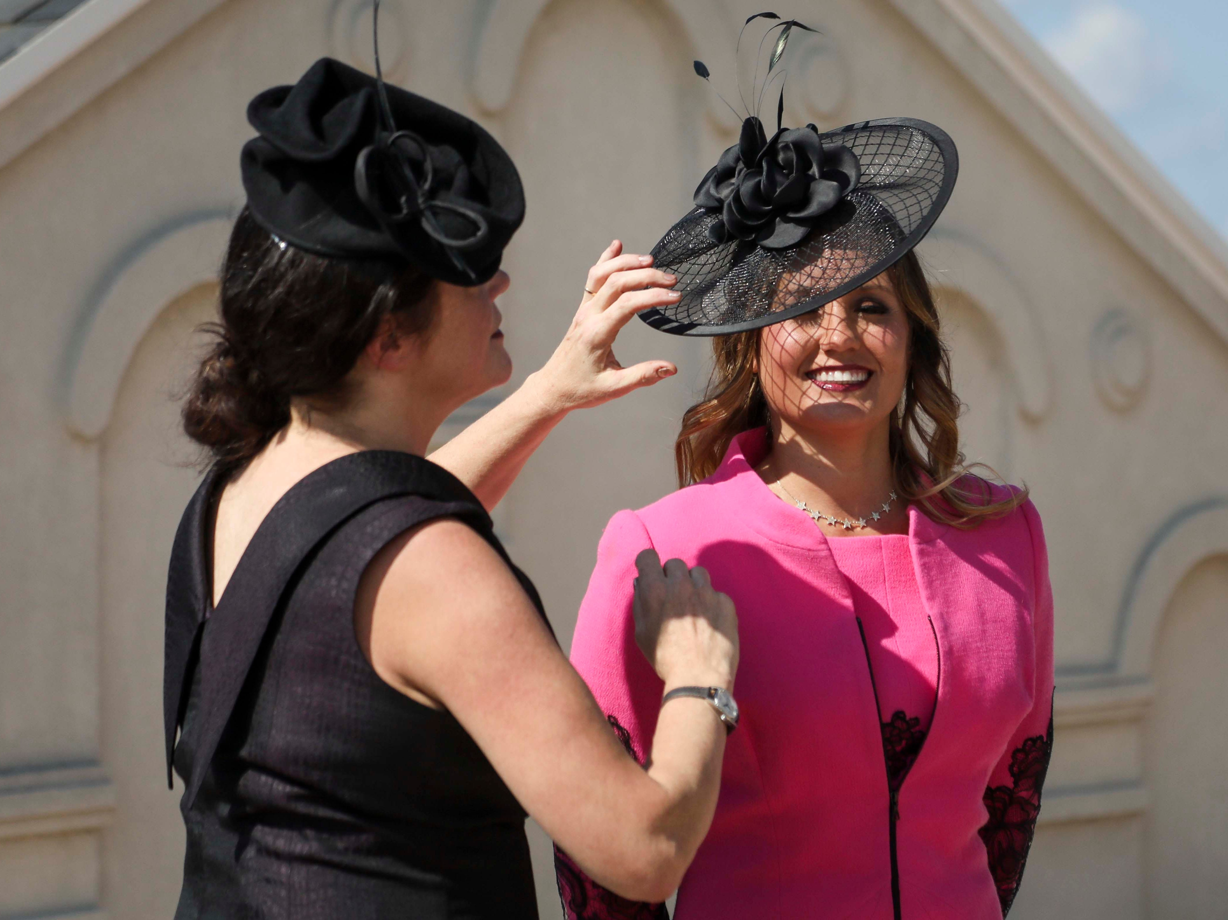 Christine Moore, left, track fashion expert and owner of Cam Hats, places one of her handmade hats on Candice Isa, right, during an interview with the Courier Journal ahead of the Breeders Cup (November 3) at Churchill Downs on Wednesday, October 3, 2018.