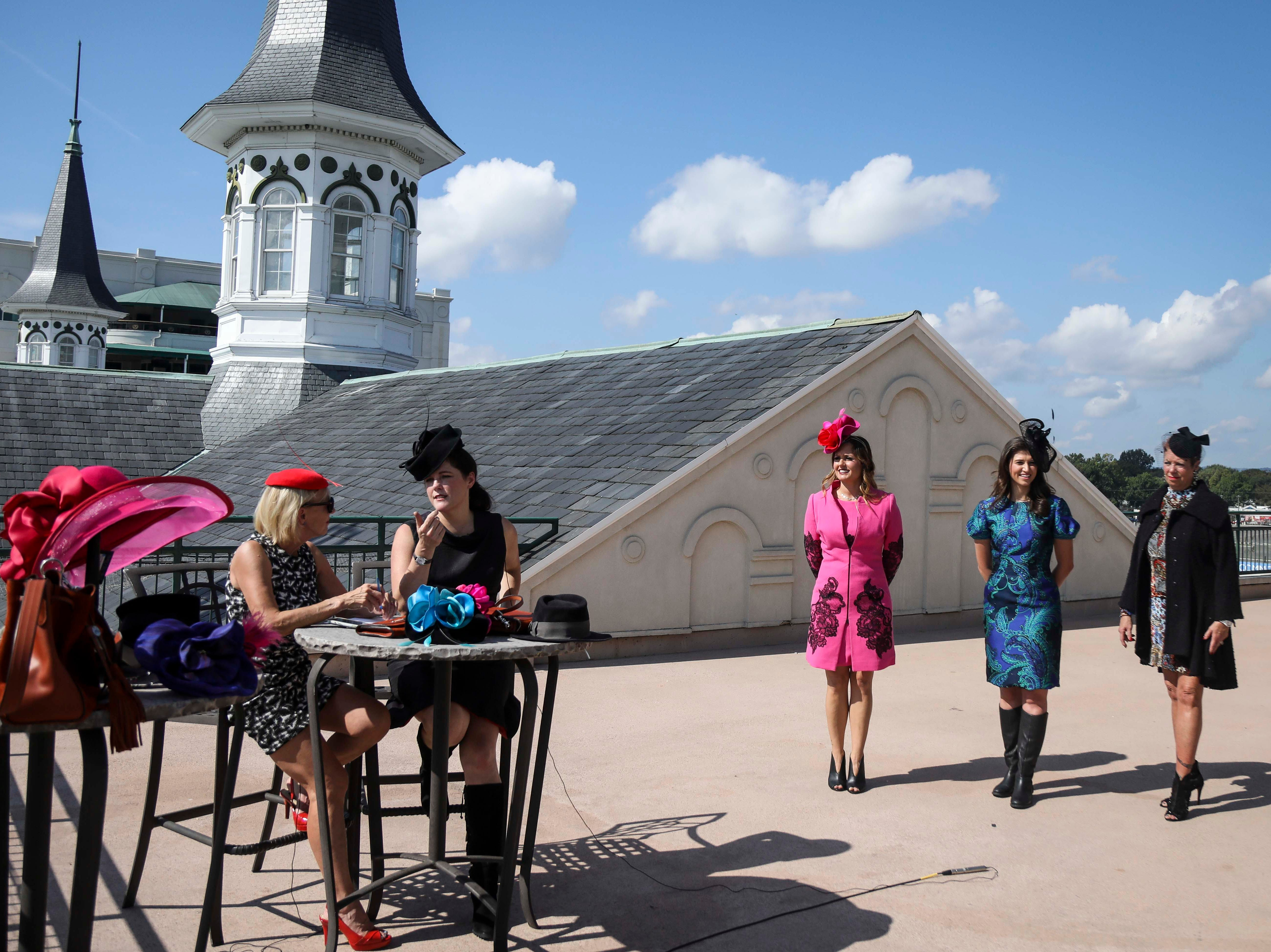 Kirby Adams, left, and Christine Moore, right, track fashion expert and owner of Cam Hats, discuss track fashion during an interview with the Courier Journal ahead of the Breeders Cup (November 3) while (from left to right) Candice Isa, Katie Bouchard and Patty Ethington model dresses from Lourdes Chavez and Moore 's handmade Cam Hats at Churchill Downs on Wednesday, October 3, 2018.