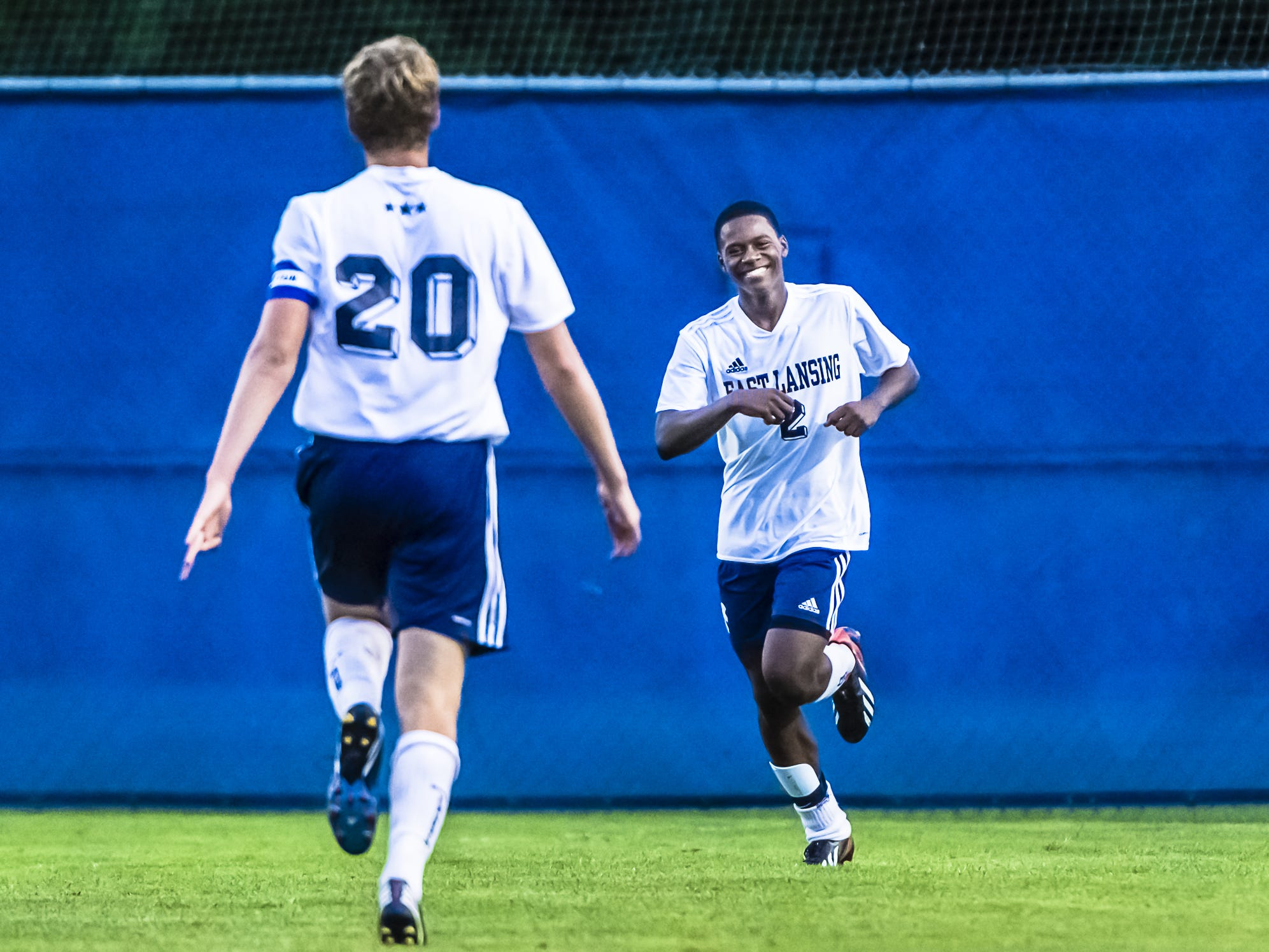 Dejuan Jones (right) of East Lansing smiles as he runs to teammate Grant Brogan after scoring what would be the game winning goal early in the 2nd half of their game with Holt Wednesday September 11, 2013 in East Lansing.  Holt would score later to narrow the Trojan lead to 3-2.