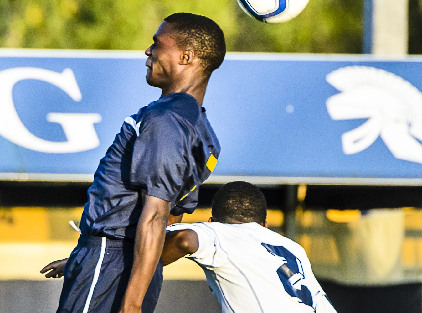 Yusef Muya (left) heads the ball away from Dejuan Jones of East Lansing during their game Tuesday September 11, 2012 in East Lansing.