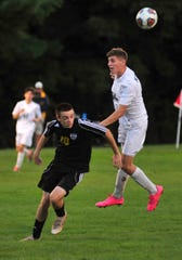 Lexington's Gavin George head butts the ball in front of Madison's Dylan Metz on Tuesday.