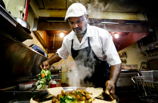 Blue Nile Ethiopian Kitchen owner Ermyias Shiberou prepares an Ethiopian Corniece Platter with spicy lamb.