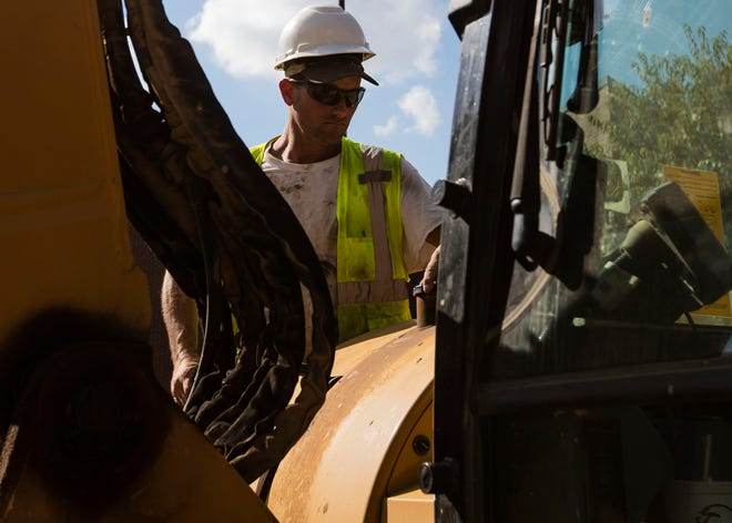 A construction worker works on piping and plumbing in front of Bartlett High School on Oct. 3.