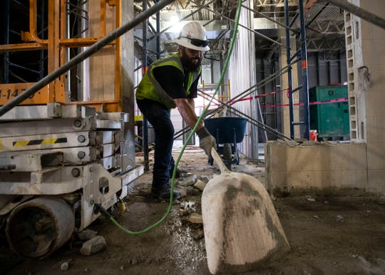 Damian Applegate moves shovels concrete in Bartlett High School as part of the $60 million renovation Monday October 3, 2018.