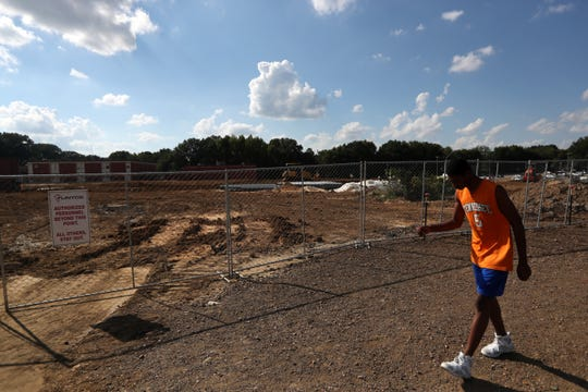 A student walks along the field outside of Bartlett High School, which is undergoing a $60 million renovation, on Wednesday, Oct. 3, 2018. The renovation started this June and is set to be completed by the beginning of the 2020 school year.