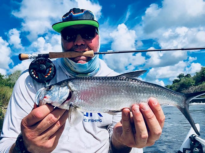 Capt. Rik Treamer sharing one of his Ten Thousand Islands tarpon catches. Treamer caught it on a fly rod and released it alive after a quick snap.