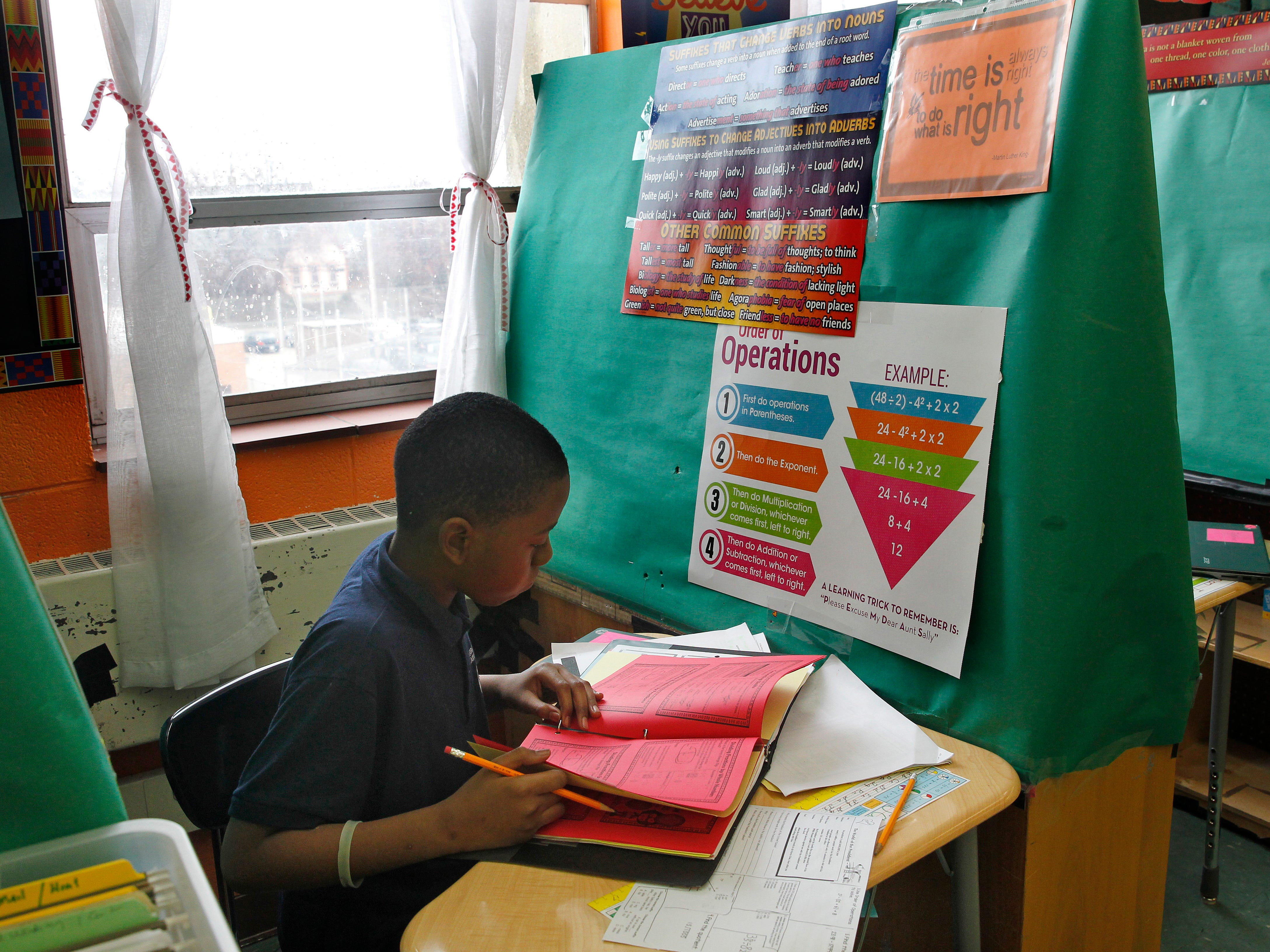 Jamarrius Jordan, who is in the sixth grade, on April 13 works on class assignment in one of the private work spaces created by his teacher Angela Kaper.