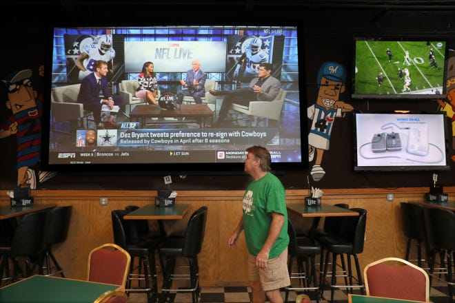 Patrick Guenther, co-owner of Kelly's Bleachers, checks a large-screen TV in his bar.