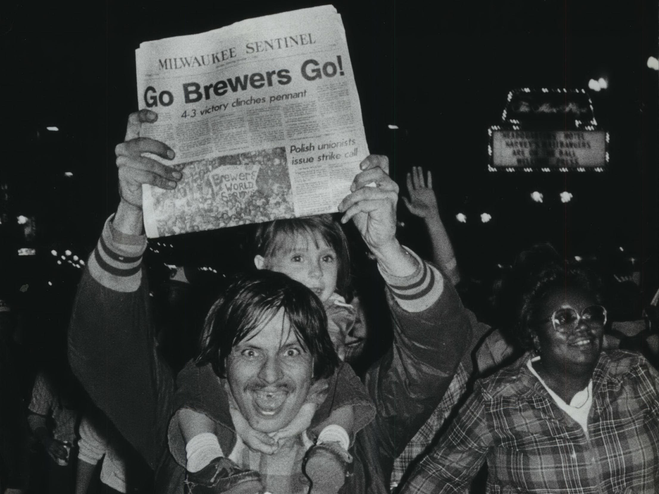 A fan joins the celebration on Wisconsin avenue after the Brewers won the American League pennant on Oct. 10, 1982. In addition to a child, he held aloft an early addition of the next morning's Milwaukee Sentinel.