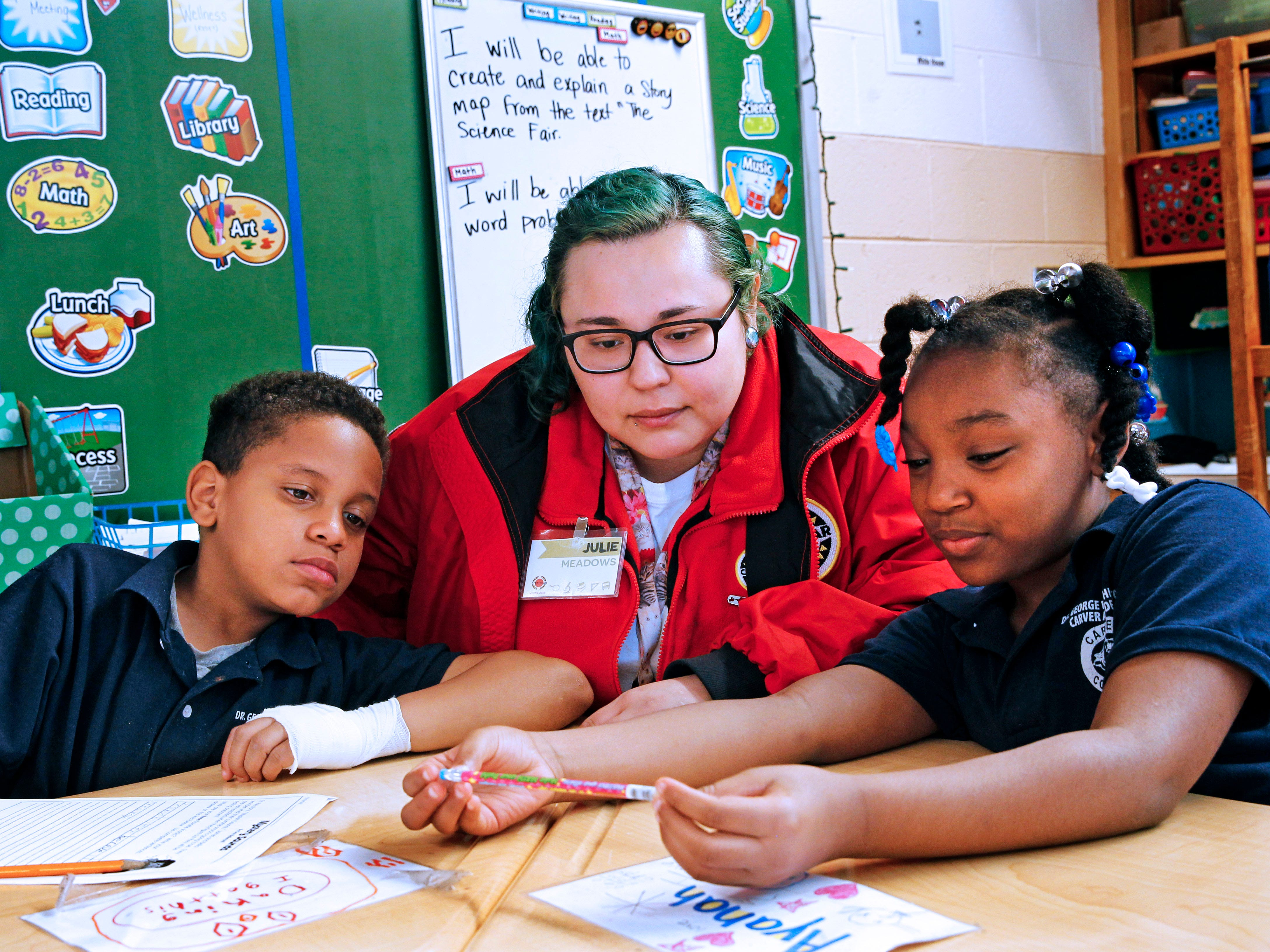 City Year Americorp staffer Julie Meadow (center) works with Daking (cq) Bogan-Clark, 9, (left) and Ayanah (cq) Harvey, 8, at Carver Academy.