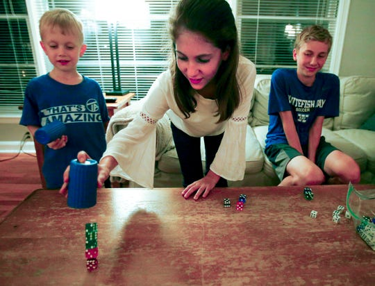 Isabel End, 11, shows her dice stacking skill with siblings Colin, 5, and Matthew, 14, on a living room coffee table at their Whitefish Bay home.