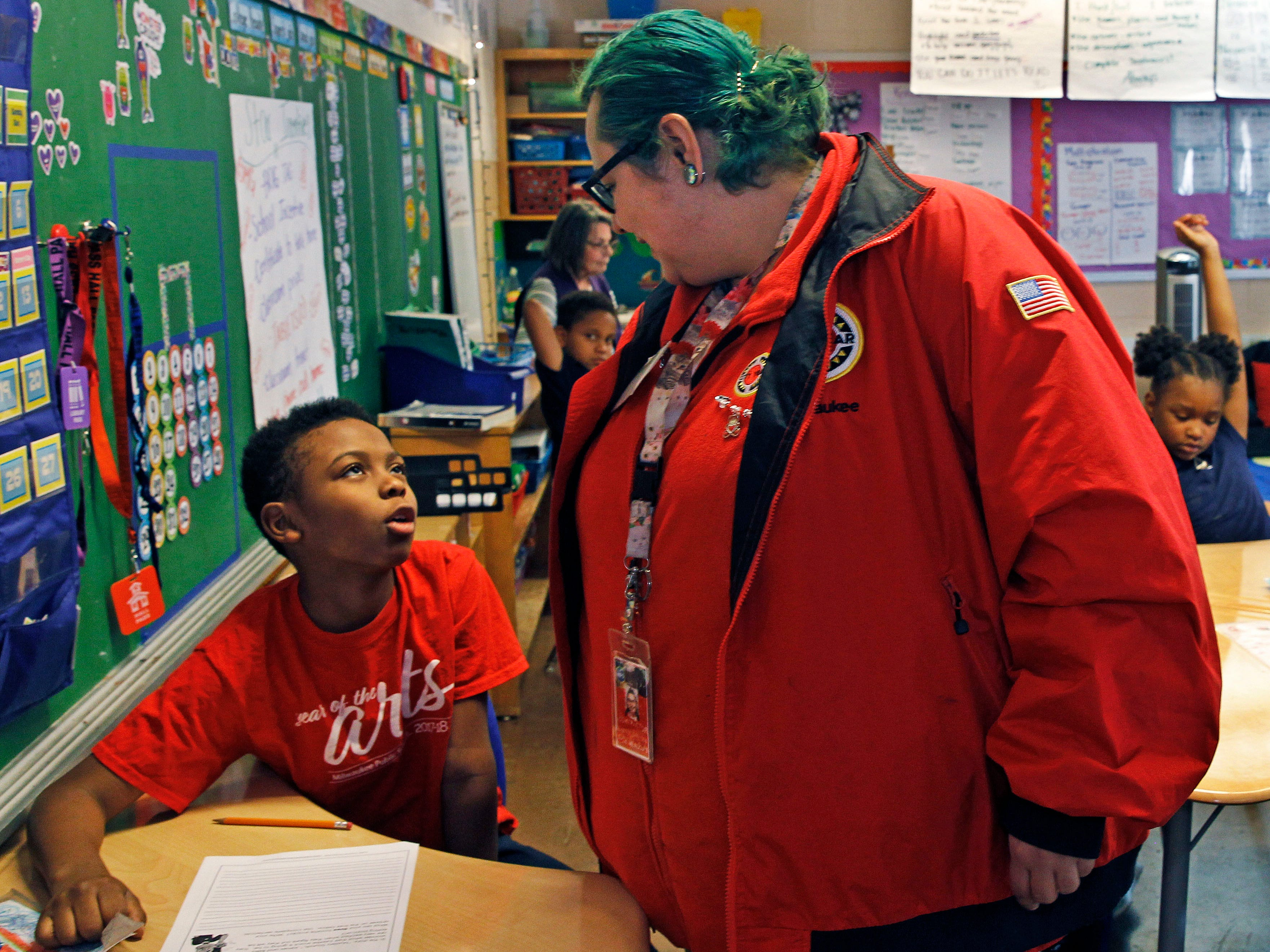 City Year Americorp staffer Julie Meadow  works with third-grader Meko Spann, 9, in May at Carver Academy.