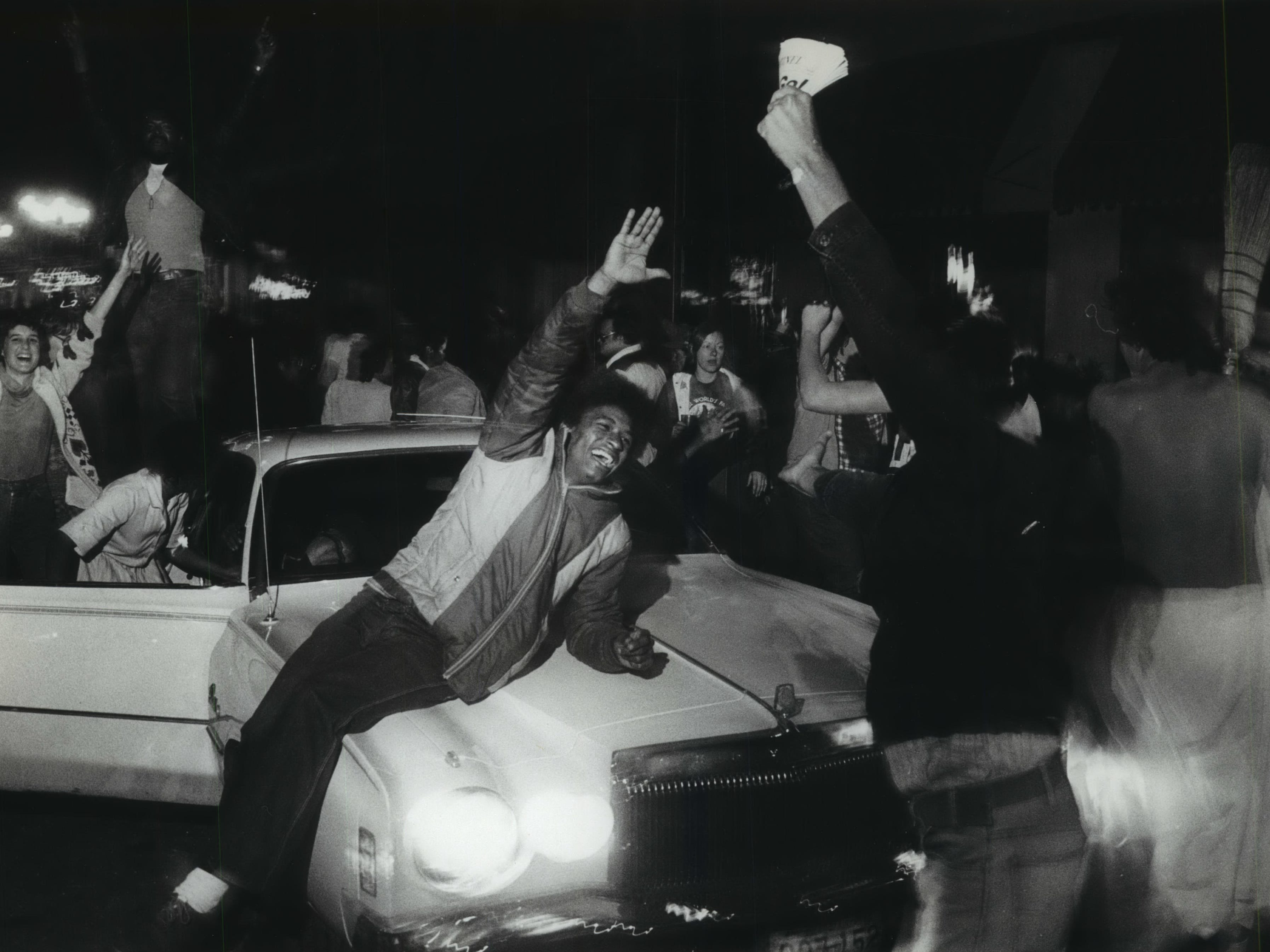 Fans climb out of and on top of cars along Wisconsin Avenue as they celebrate the Milwaukee Brewers winning the American League pennant on Oct. 10, 1982.