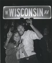 Two fans display a street sign that had been torn down during the celebration of the Milwaukee Brewers' winning the American League pennant on Oct. 10, 1982. The party on Wisconsin Avenue, from County Stadium to the lakefront, lasted for more than seven hours.