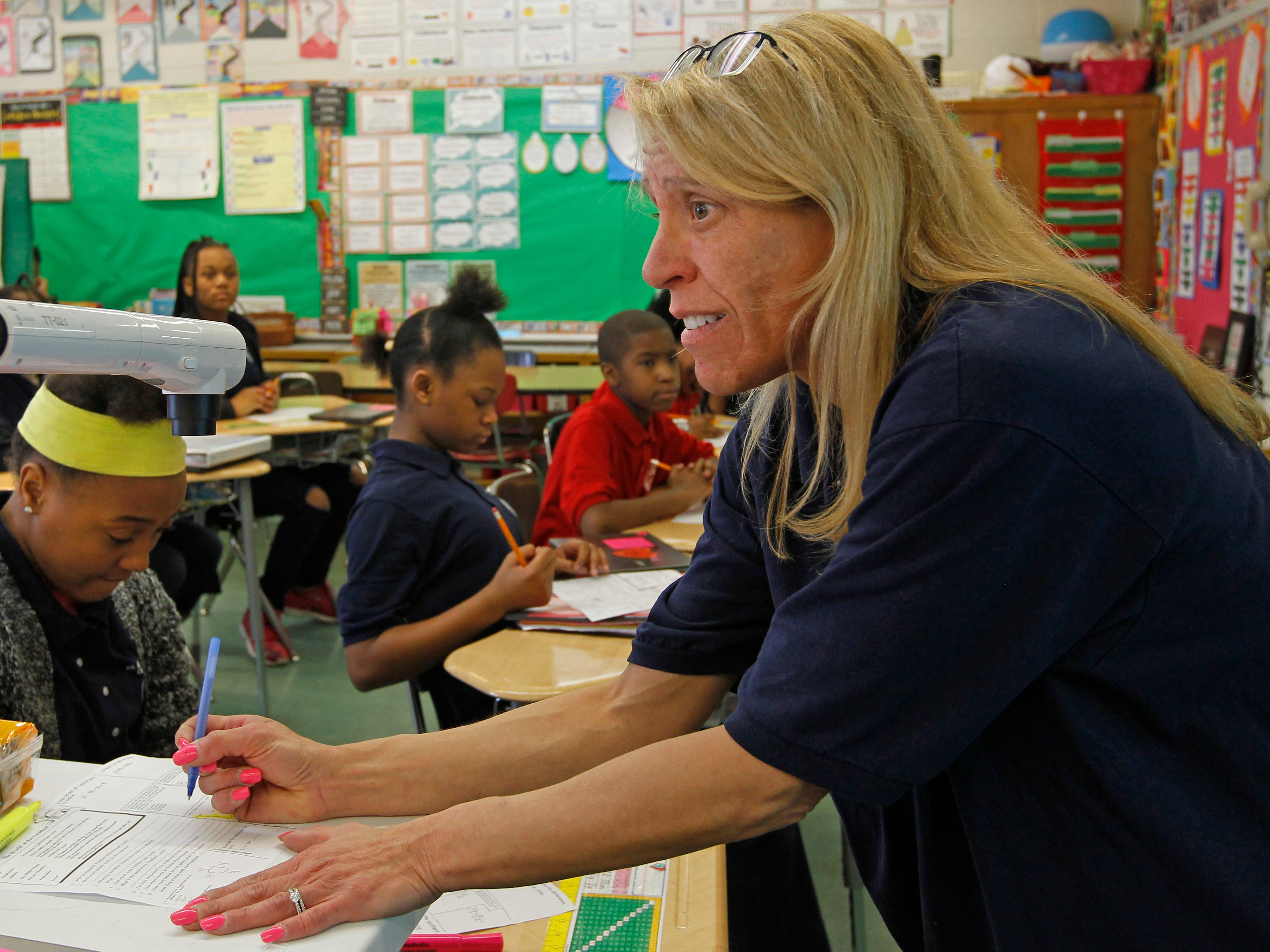 Sixth grade teacher Angela Kaper reviews math lesson with students April 13 at Carver Academy.