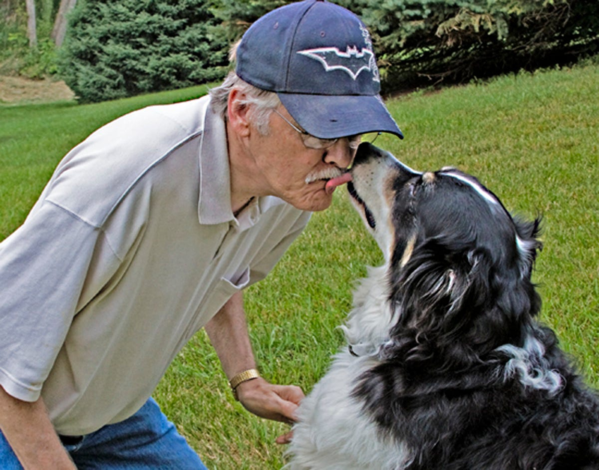 Bill Janz shares a kiss with his dog Lightning in this 2013 photo. Janz, a former columnist with the Milwaukee Sentinel and Milwaukee Journal Sentinel, credits Lightning with saving his life.