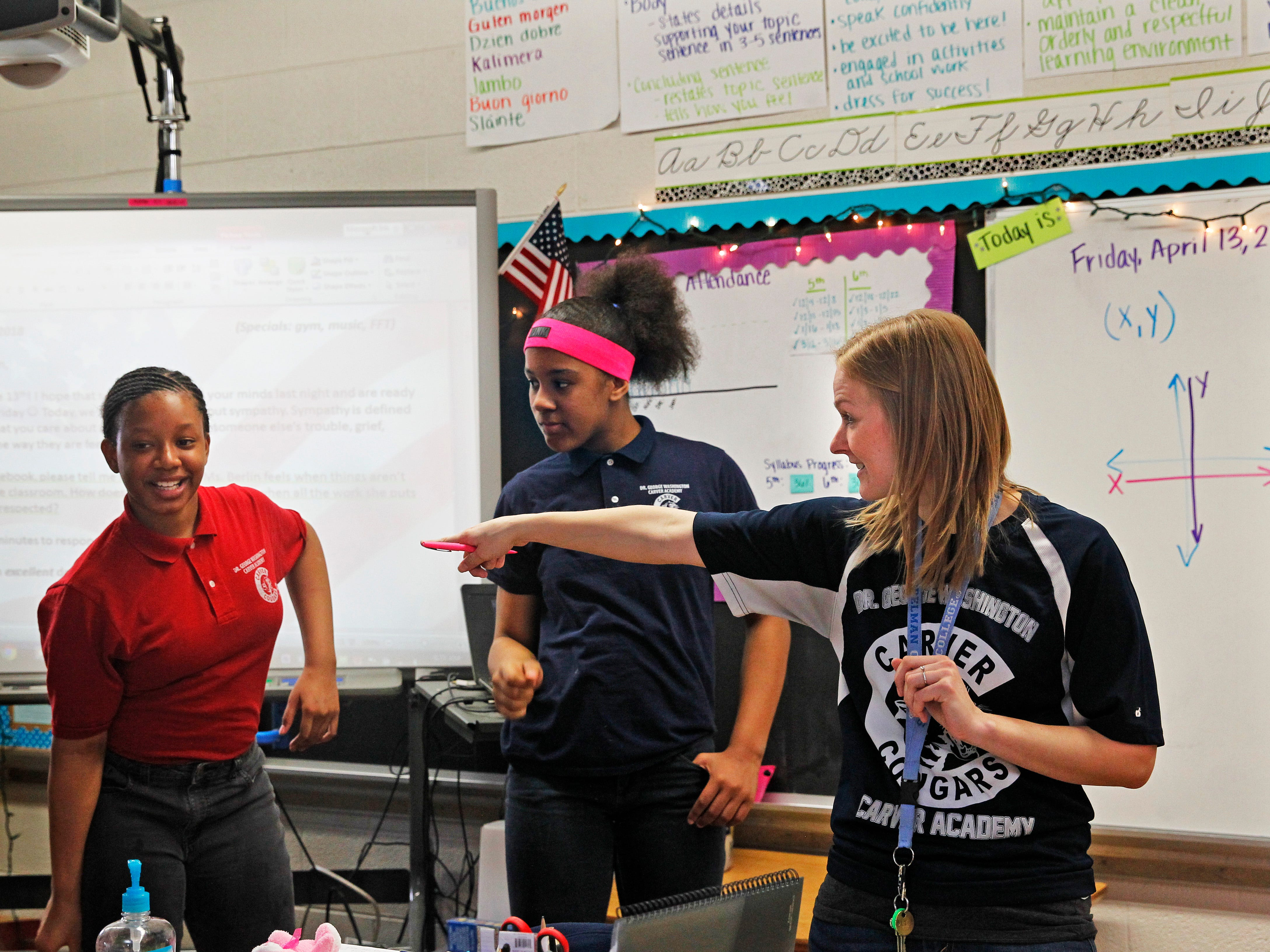 "Sixth-grader Trinity Coffey (left) and fifth-grader Jainyla Herrington (center) participate on April 13 with their teacher Megan Berlin (right) in a ""Circle of Power and Respect"" exercise. The activity helps build strong social relations among students and faculty."