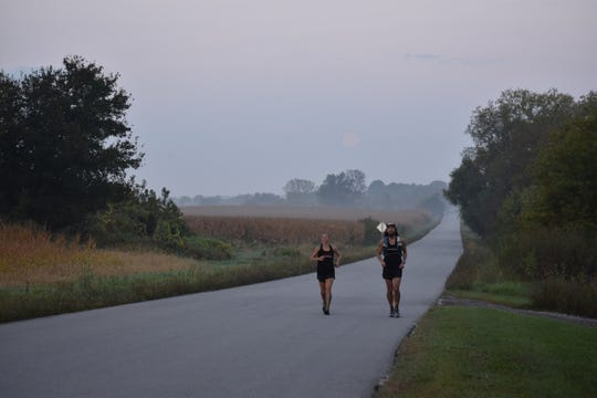 Annie Weiss runs with Kevin Cannaday who helps her keep pace while she runs the Ice Age Trail. About 500 miles of the trail aren't completely built, so she had to run on pavement. She beat a record for the fastest time on Sunday, Sept. 30 at 1 a.m.