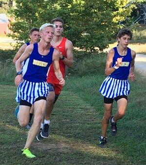 Mountain Home's Whit Lawrence (left), Bob Allen (back) and Andrew Westphal (right) compete Tuesday at Cave City.