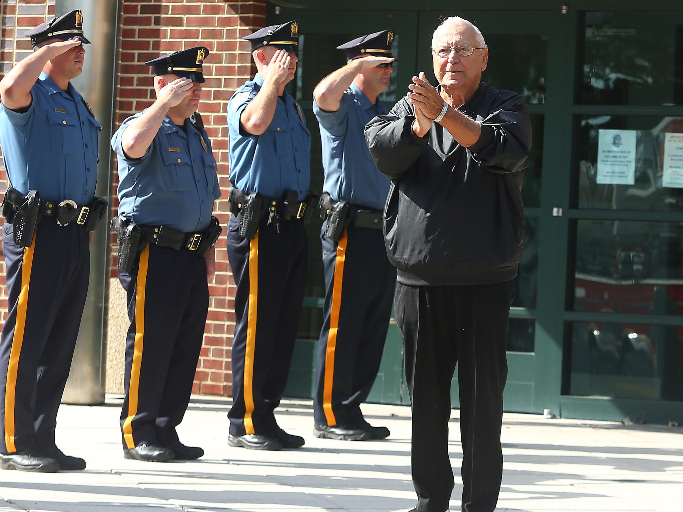 Steve Bolcar comes out of the Hanover Municipal Building to applause during his Police-style clapout for retirement of the 60-year officer and crossing guard. October 3, 2018, Hanover, NJ