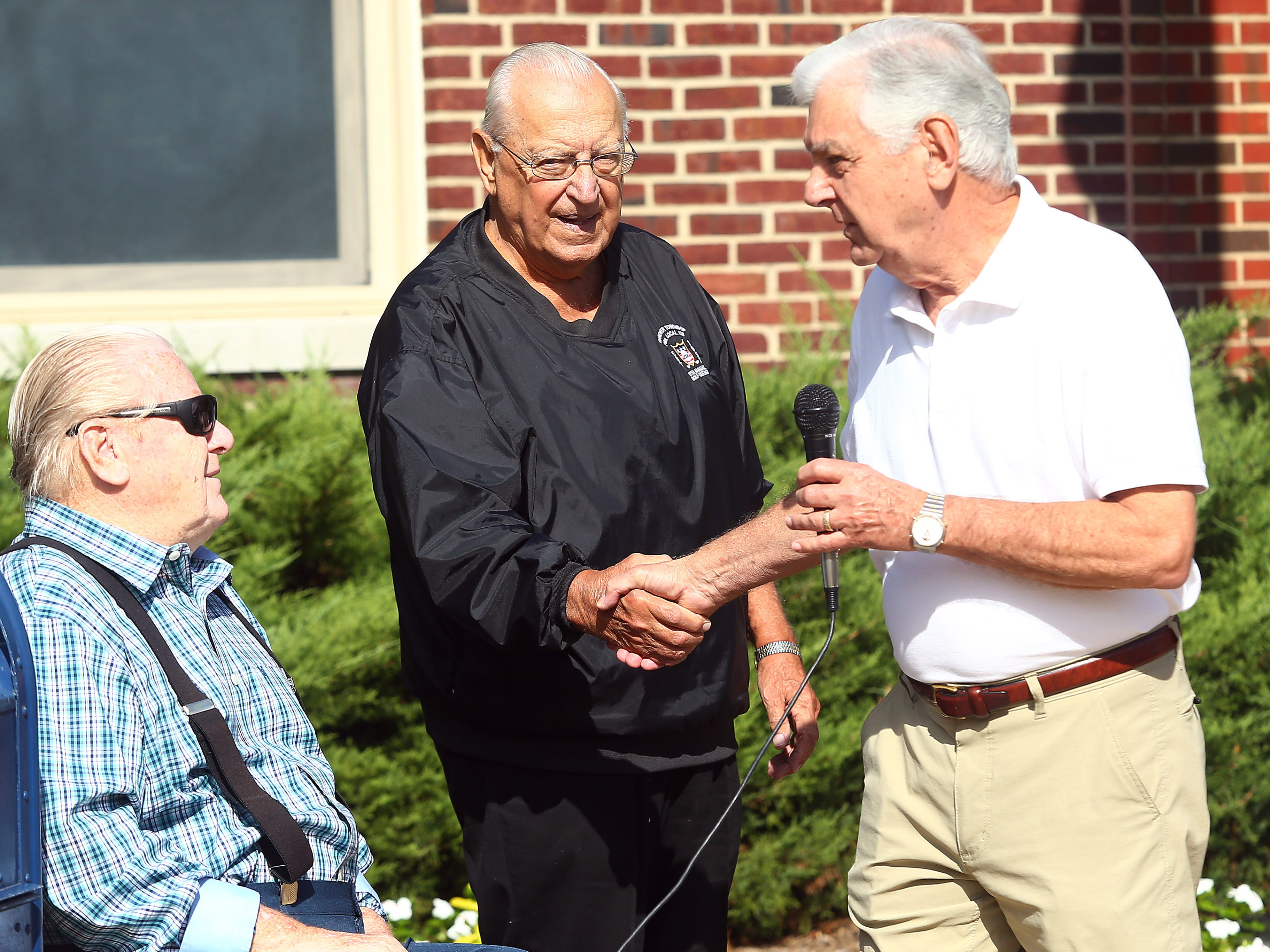 Steve Bolcar shakes hands with Hanover Mayor Ronald Francioli as life-long friend Joseph Mihalko looks on at the Hanover Municipal Building. Bolcar was given a police-style clapout for retirement of the 60-year officer and crossing guard. October 3, 2018, Hanover, NJ