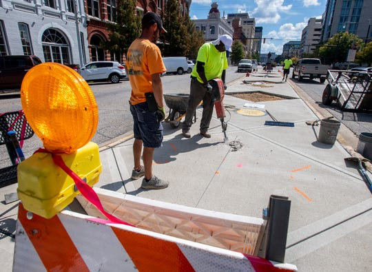 Workers from ConCreations install quotes in the sidewalk to the Riverwalk on Commerce Street in Montgomery, Ala., on Wednesday October 3, 2018.