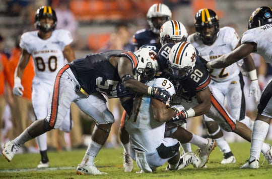 Auburn's Deshaun Davis (57) and Auburn's Jeremiah Dinson (20) take down Southern Miss' Tim Jones (87) at Jordan-Hare Stadium in Auburn, Ala., on Saturday, Sept. 29, 2018. Auburn defeated  Southern Miss 24-13.