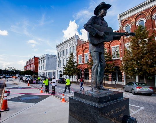 Workers from ConCreations install quoters in the sidewalk to the Riverwalk on Commerce Street in Montgomery, Ala., on Wednesday October 3, 2018.