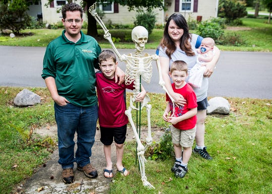 The Crigger family tells a different story each day with a group of Halloween skeletons they move into position after sunset at their Muncie home.