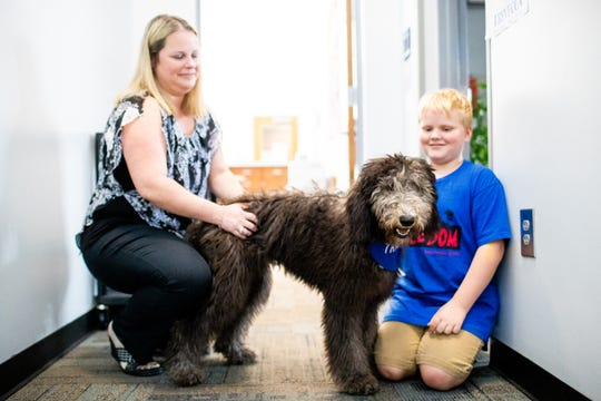 Assistant Principal Ashley McCoy and her son Carson, 10, play with Mattie while she is in training to become a therapy dog for the students at Johnson Elementary School Tuesday, Oct. 2, 2018, in Franklin, Tenn.