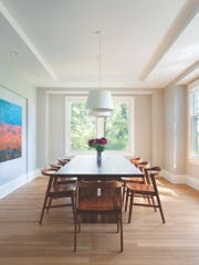 Artworks by various family members get a spotlight in the recessed dining room wall niche.