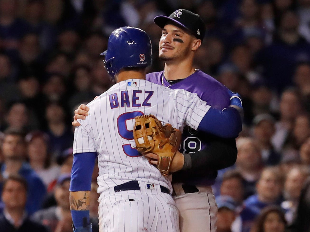 Oct 2, 2018; Chicago, IL, USA; Chicago Cubs shortstop Javier Baez (9) hugs Colorado Rockies third baseman Nolan Arenado (28) after being tagged out in the 11th inning in the 2018 National League wild card playoff baseball game at Wrigley Field.