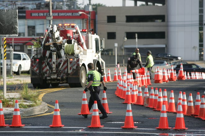 Sept. 13, 2013: A Port Authority police officer and maintenance crews remove the traffic cones, opening all tollbooths and lanes to the George Washington Bridge, at the intersection of Martha Washington Way and Bruce Reynolds Boulevard.