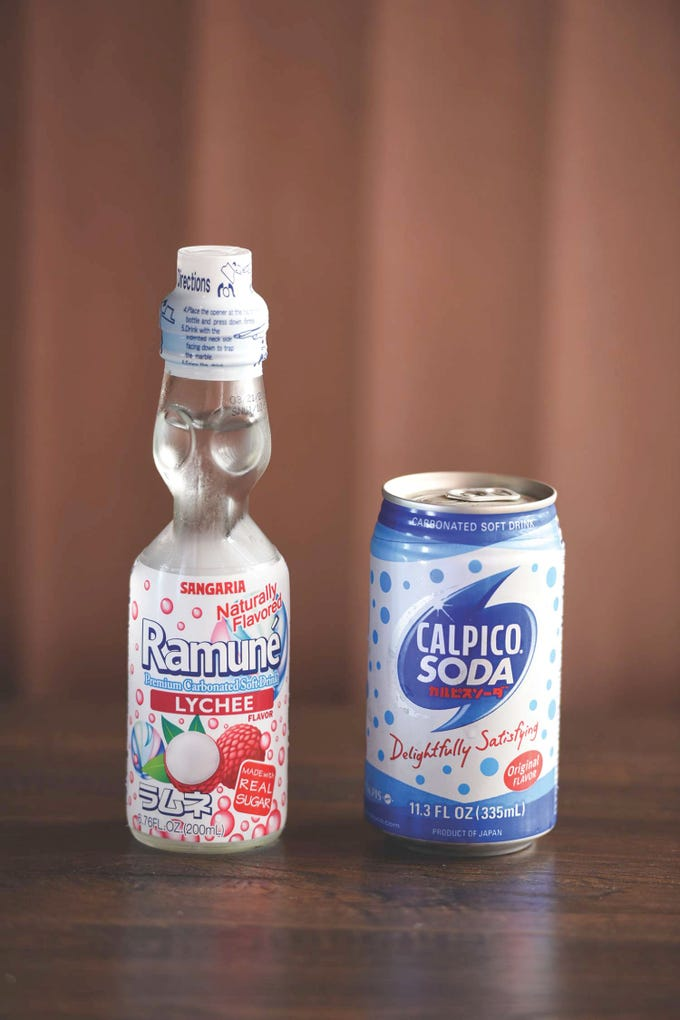Bottle of Ramune lychee soda (L) and a can of Japanese Calpico soft drink (R), photographed at Dozo Sushi & Asian Cuisine in Livingston