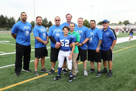 Josh Piperato, front center, with his mother Ana (in green) and the North Arlington Junior Vikings football staff.