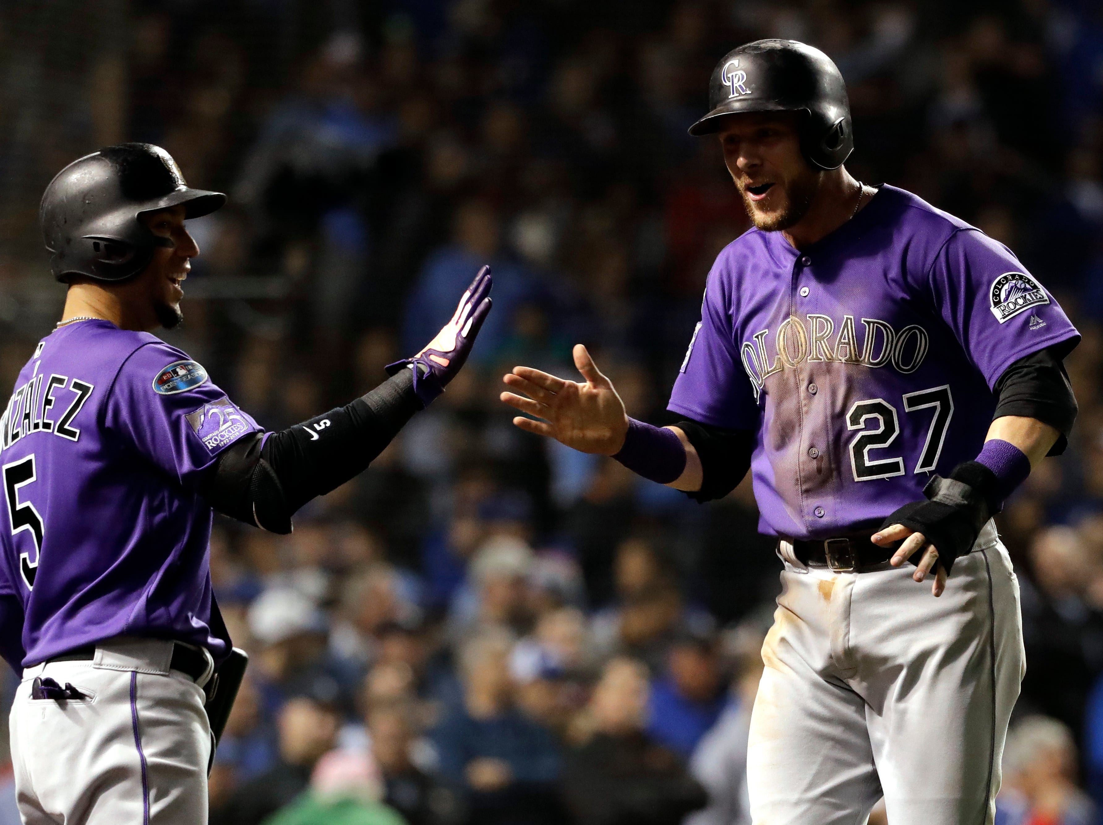 Colorado Rockies' Trevor Story, right, celebrates with Carlos Gonzalez after scoring on a one-run single by Tony Wolters during the 13th inning of the National League wild-card playoff baseball game against the Chicago Cubs, Tuesday, Oct. 2, 2018, in Chicago. (AP Photo/Nam Y. Huh)