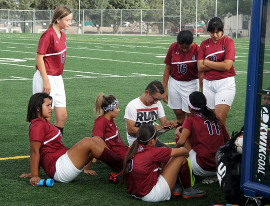 Deming High Soccer Coach Carlos Astudillo huddles with the Lady 'Cats during half time of Tuesday's District 3-5A match with Alamogordo High.