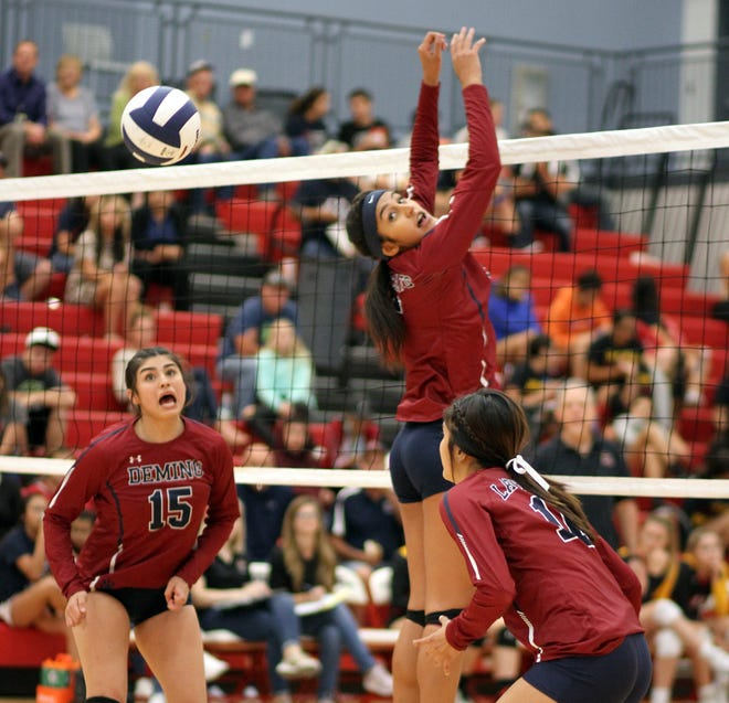 Senior middle blocker Vanessa Garcia looks back at the deflected ball off her block while teammates Jolene Perez (15) and Evelyn Ramirez look on.