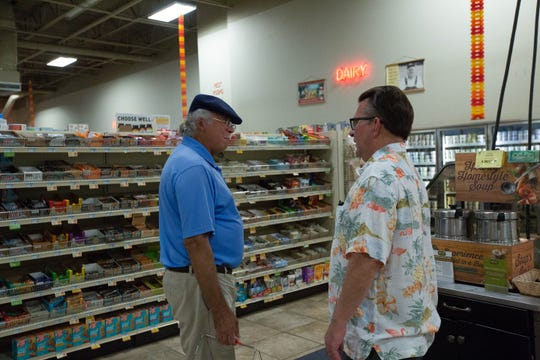 Bob Baur, right, now the owner of Toucan Market, talks with customer Tony Lopez, left, Wednesday October 3, 2018. Toucan was going out of business but is now staying open after Baur bought out his former co-owner.