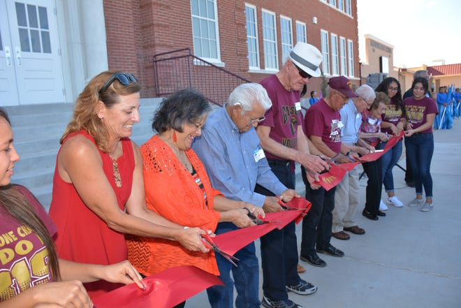 Gadsden Independent School District board members Maria Saenz, left, and Jennifer Viramontes assist alumni who were invited to cut the ribbon at the grand reopening of Gadsden High Old English Building on Thursday, Sept. 27.