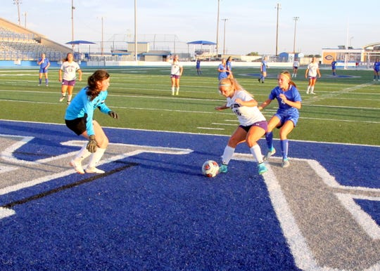 Clovis' Kasey Ayre (16) prevents Alexa Dugan, right, from attempting a shot during the first half of Tuesday's match at Caveman Stadium.