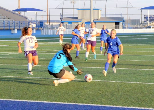 Clovis goalie Hannah Howell (55) prevents Carlsbad's Alexa Dugan (4) from scoring in the first half of Tuesday's match. Clovis' two goalies made 17 total saves, ending the match in a 0-0 tie.
