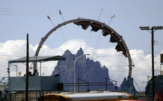 Shiprock is seen through a carnival ride during Youth Day at the Northern Navajo Nation Fair on Thursday, Oct. 6 2011 at the Northern Navajo Nation Fairgrounds in Shiprock.