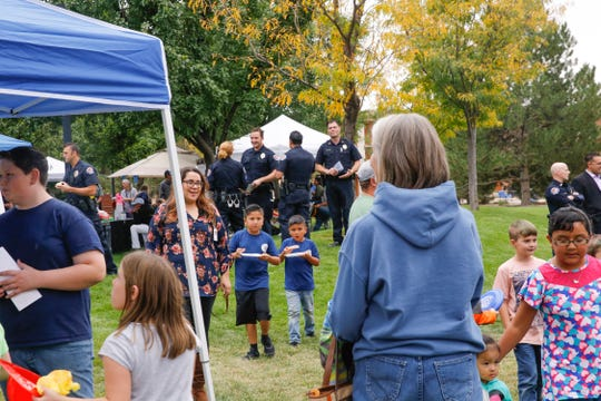 Community members and local law enforcement officers attend the annual National Night Out hosted by the Farmington Police Department, Tuesday, Oct. 2, 2018 at Berg Park in Farmington.