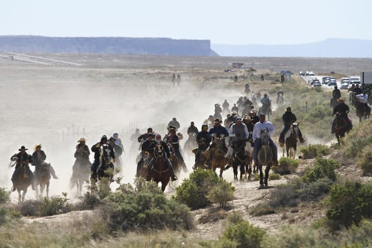 Horse riders take part in the Traditional Trail Ride , Friday, Oct. 4, 2013, along U.S. Highway 491, as they head towards the Northern Navajo Nation Fair in Shiprock.